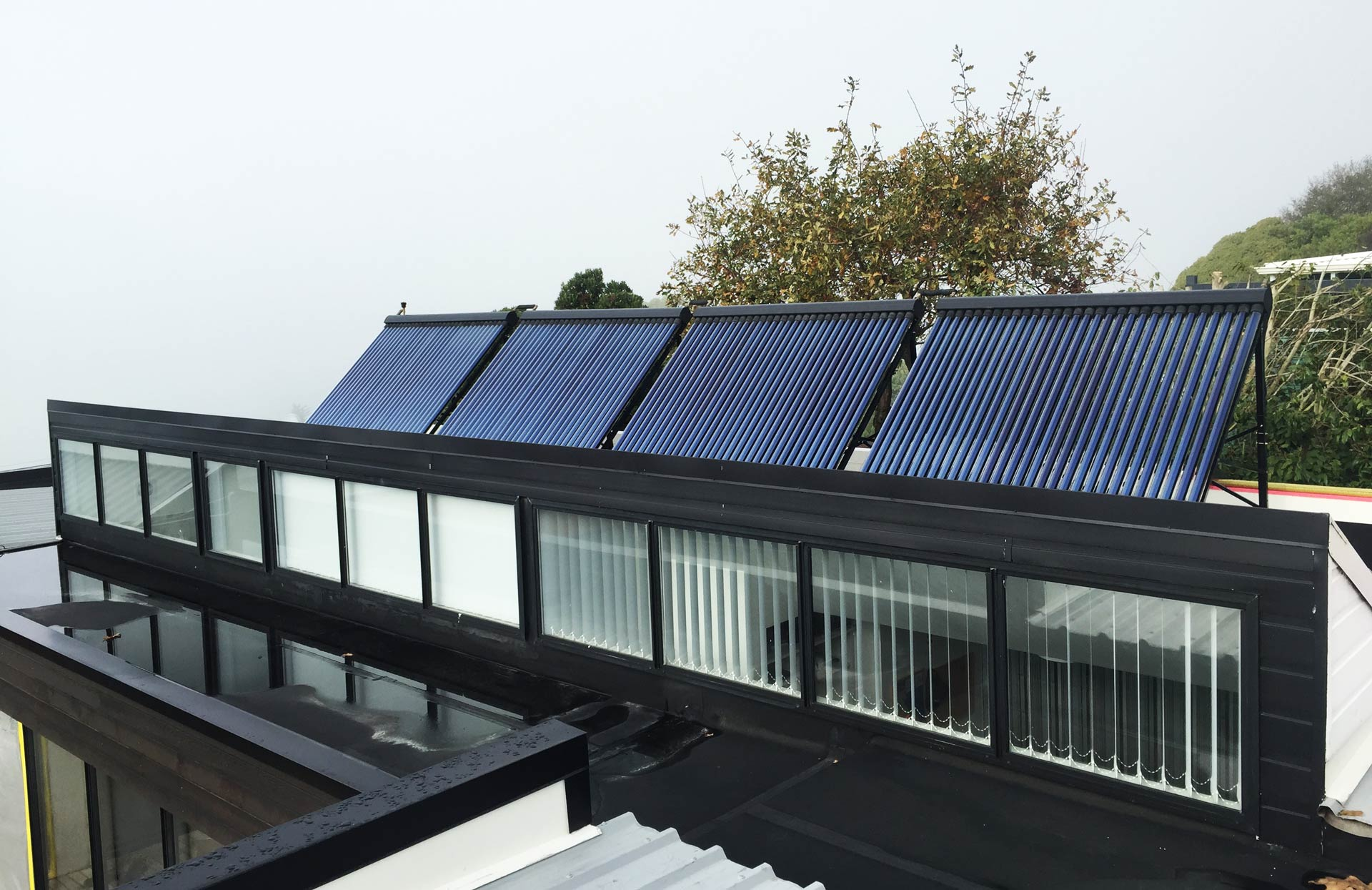 4 solar thermal systems on a roof with 11 windows and black roof